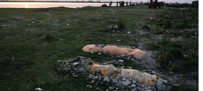 تصاویر بیرون آمدن اجساد کرونایی از قبر بر اثر بارش باران در هند,عکس های لباس اجساد دفن شده در قبرهای کمعمق هند,تصاویری از اجساد کرونایی در هند